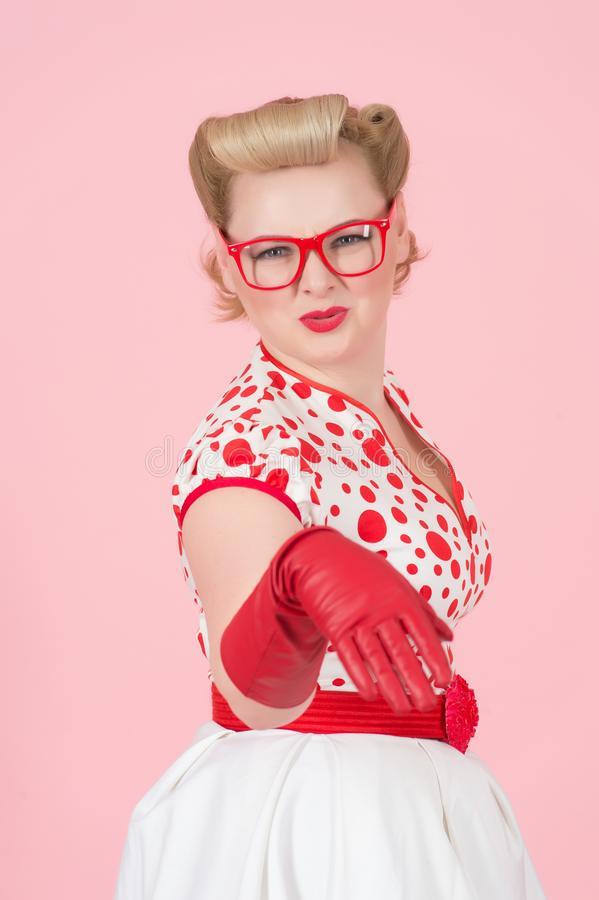 Hey you buddy! Shocked young blonde woman pointing by hand in red gloves at camera and open mouth. Studio shot of female model iso stock photos