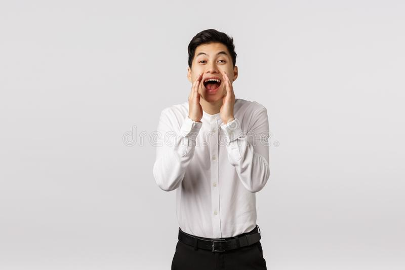 Hey you come here. Cheerful smiling happy asian guy searching new employees to company, hire, holding hands near opened. Mouth shouting name, searching someone stock photography