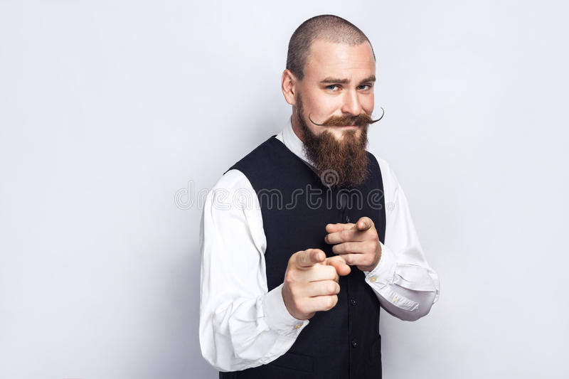 Hey you. Handsome businessman with beard and handlebar mustache looking at camera. Studio shot, on gray background stock image