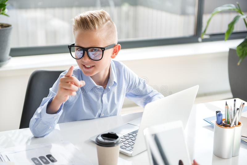 Positive cute child is laboring on laptop royalty free stock image
