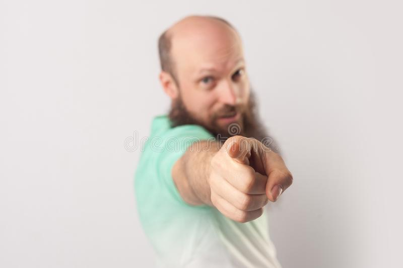 Hey you! Portrait of funny middle aged bald man with long beard in light green t-shirt standing, pointing and looking at camera royalty free stock photo
