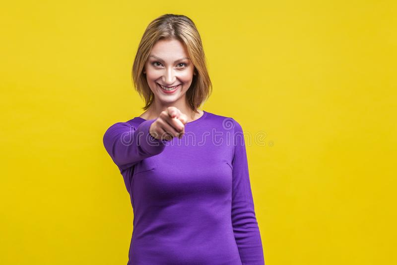 Hey you! Portrait of positive elegant woman pointing at camera and smiling. isolated on yellow background stock photography