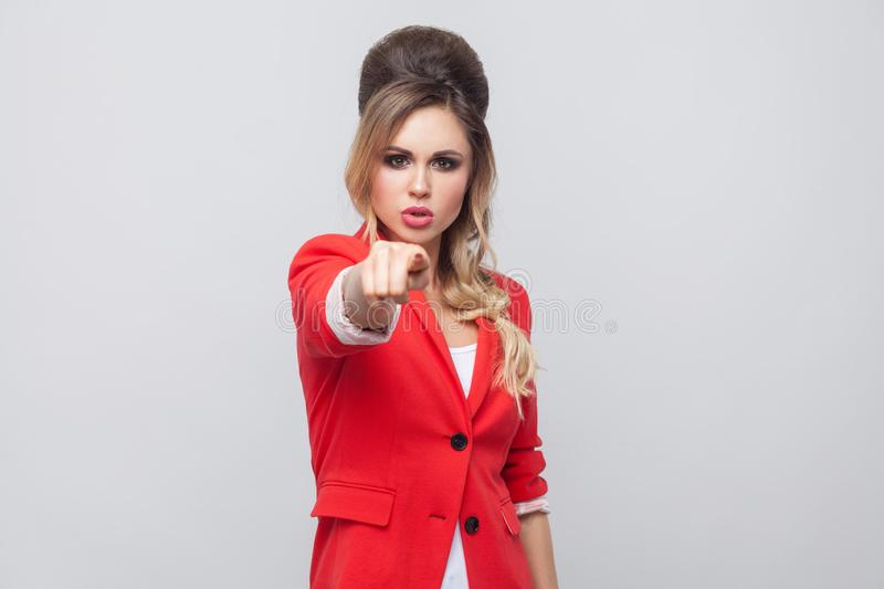 Hey you. Portrait of serious beautiful business lady with hairstyle and makeup in red fancy blazer, standing, looking at pointing. At camera. indoor studio shot stock photo