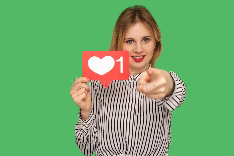 Hey you, put like to content! Pretty girl with red lips in glamour striped blouse holding social media heart icon. Hey you, put like to content! Pretty girl with stock image