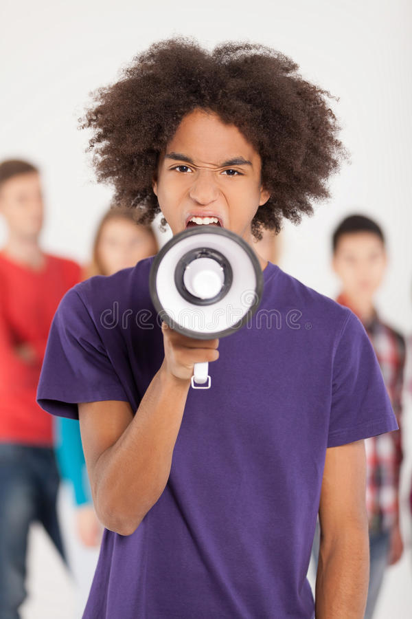 Hey you!. Young African teenager shouting at megaphone while his friends standing on background stock photo