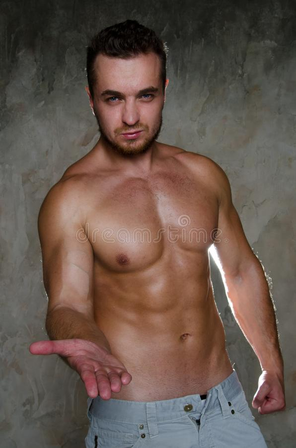 Hey. Young man holds out his hand. Friendly muscular man without a shirt royalty free stock photography