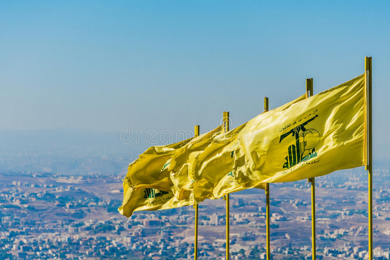 Hezbollah flags fly over southern Lebanon. Hezbollah flags fly over southern Lebanese land liberated from occupying Israeli forces by Hezbollah in 2000. The stock photo