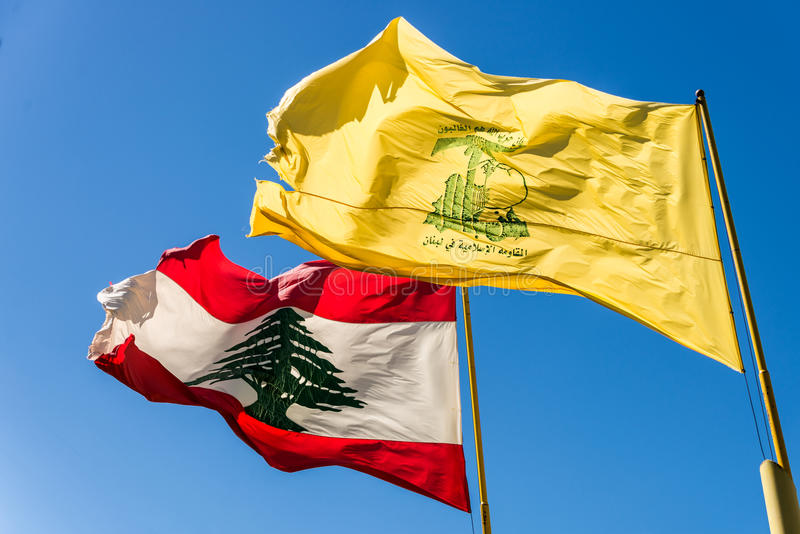 Hezbollah and Lebanese flags fly side by side. A Hezbollah flag flies with the Lebanese flag at the Mleeta Landmark Museum. The Arabic text above the Hezbollah royalty free stock images
