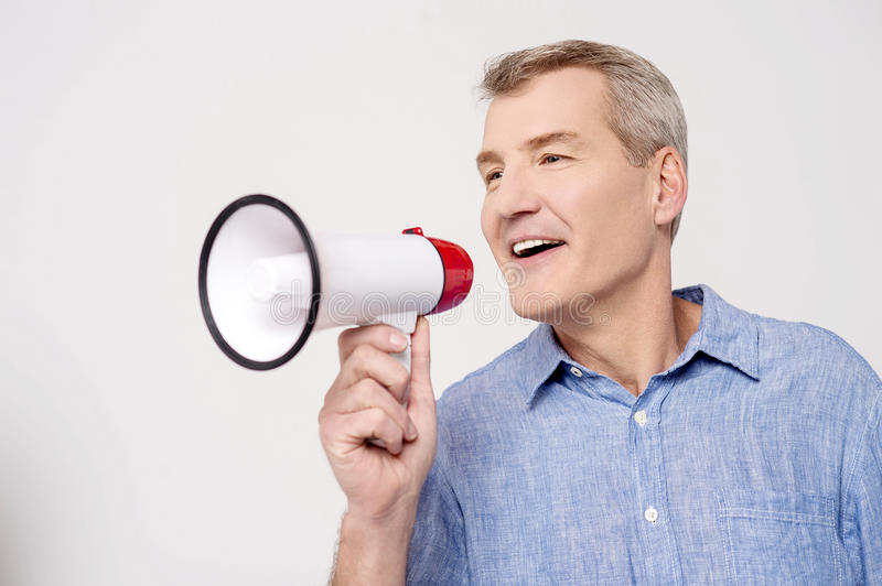 Hi everyone, listen to me !. Happy man making announcement over a bullhorn stock image