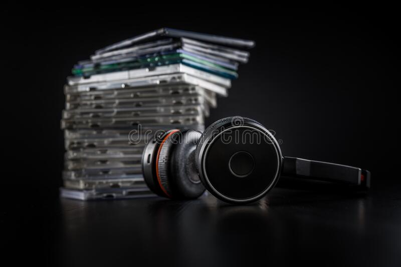 Hi-Fi headphones on stack of CDs on black background stock photography