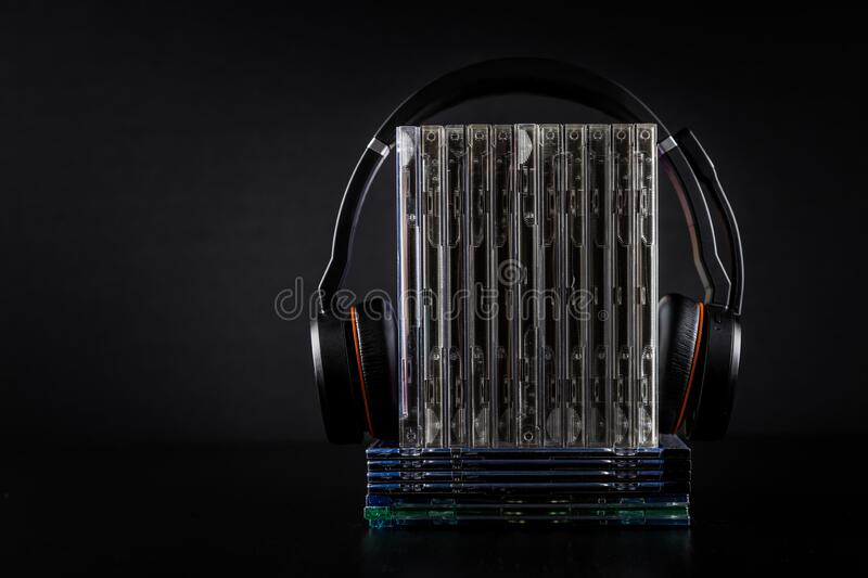Hi-Fi headphones on stack of CDs on black background royalty free stock photos