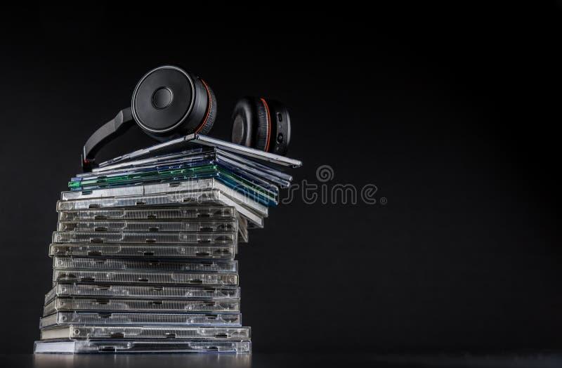 Hi-Fi headphones on stack of CDs on black background stock image