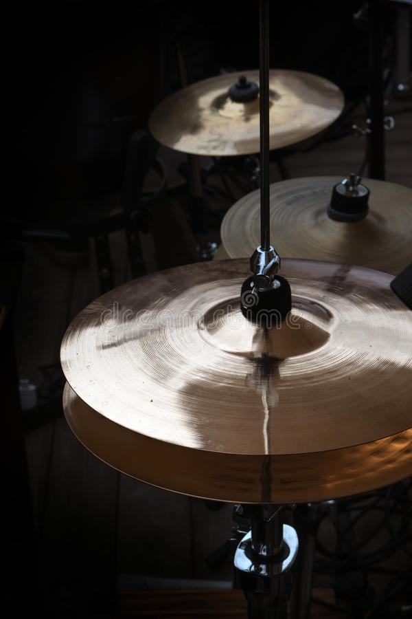 Hi-hat and cymbals on stage, musical instruments in a percussion. Drum kit for modern pop, rock, jazz, folk music and more, dark background, vertical, selected stock photography