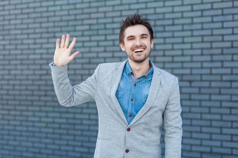 Hi, nice to see you. Portrait of happy handsome bearded man in casual style standing and looking at camera with greeting gesture royalty free stock photography