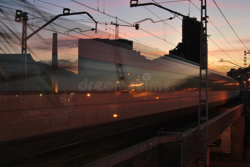 BARCELONA, SPAIN - NOVEMBER 2017: Regional train fading away passing through Hospitalet reflecting the sunset sky lights royalty free stock photo