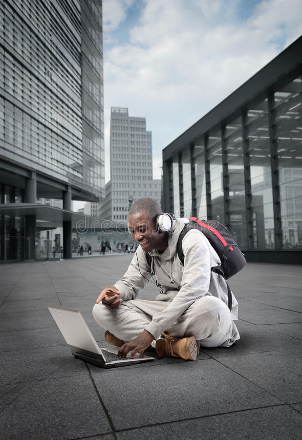 Hi-tech. Smiling african man using a laptop on a city street