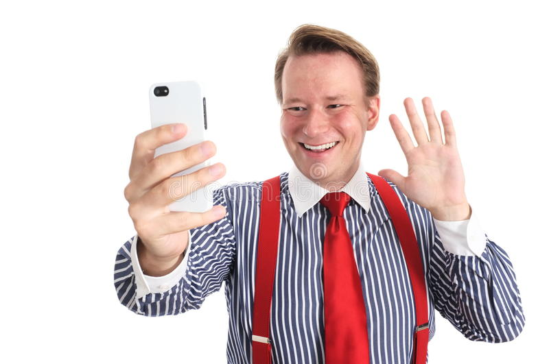 Hi there. Young businessman saying hallo to somebody through the front camera of his phone - isolated on white and retouched Could be used for telecommunications royalty free stock photography
