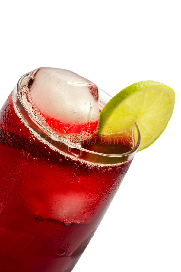 Hibiscus Iced Tea. Close-up of a glass of iced hibiscus tea with slices of lime on white background stock image