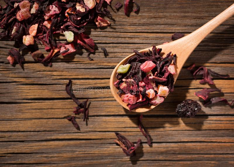 Hibiscus tea. Dry mix of red herbal and fruit tea over wooden surface royalty free stock images