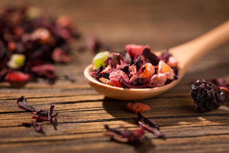 Hibiscus tea. Dry mix of red herbal and fruit tea over wooden surface stock photo