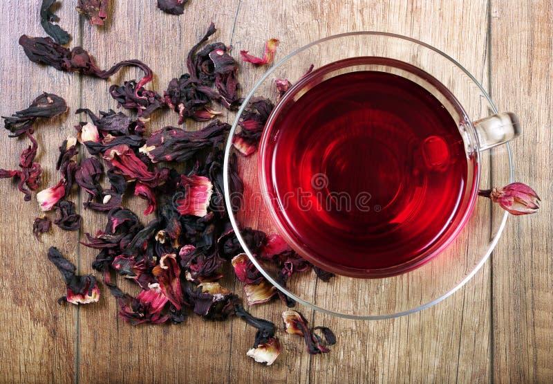 Hibiskuste i en glass kopp på en trätabell bland roskronbladen och det torra teet fotografering för bildbyråer