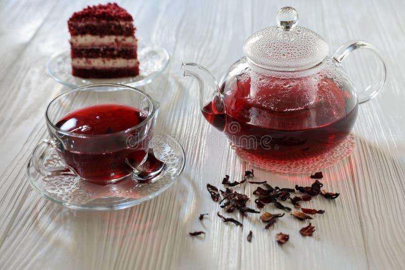 Hibiskuste i koppen och tekannan, teblad, stycke av den röda sammetkakan på vit träbakgrund arkivbilder
