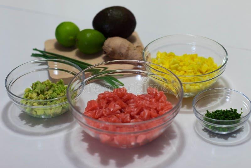 Hice esta fotografía los ingredientes tajados y preparados para cocinar un tártaro de color salmón Estos ingredientes son aguacat imagen de archivo libre de regalías