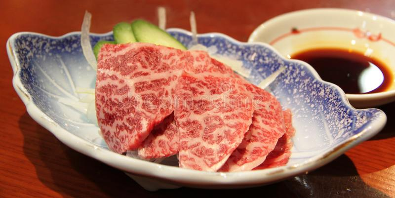 Hida beef sashimi. Served with dipping soya sauce stock photo