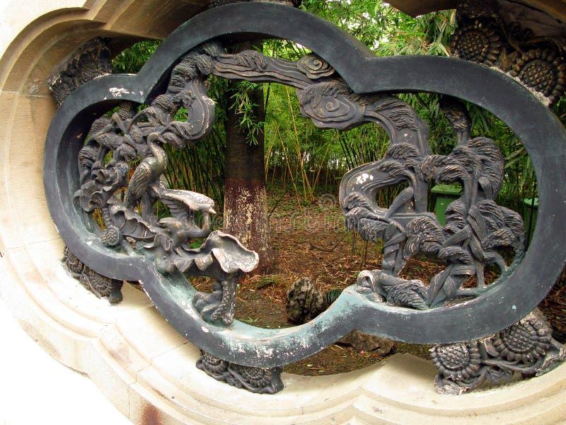 Hidden bamboo garden. Beautiful Chinese bamboo garden viewed through a decorative wall opening royalty free stock photo