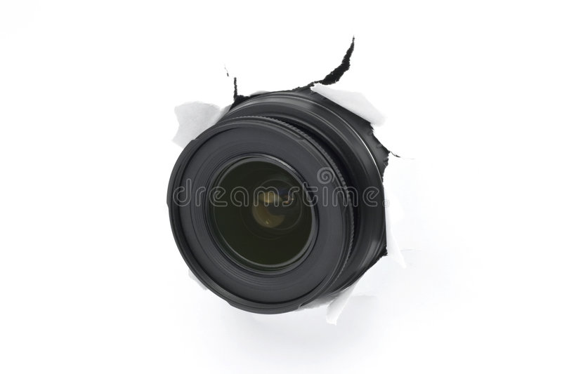 Hidden Camera. Camera lens isolated and protruding through a white paper wall. Conceptual. (All identifying information on camera lens has been removed royalty free stock photos