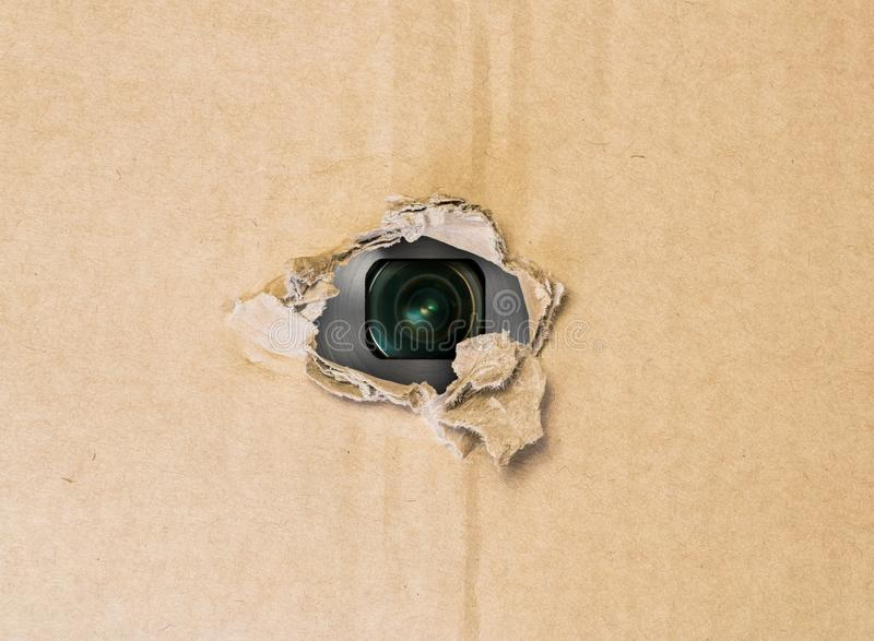 Hidden camera in torn hole in cardboard paper royalty free stock photos