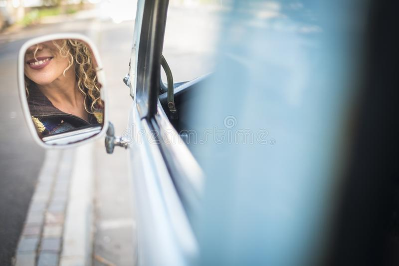 Hidden face of beautiful caucasian young blonde woman in the mirror of a old blue van - concept of travel and drive for female royalty free stock photography