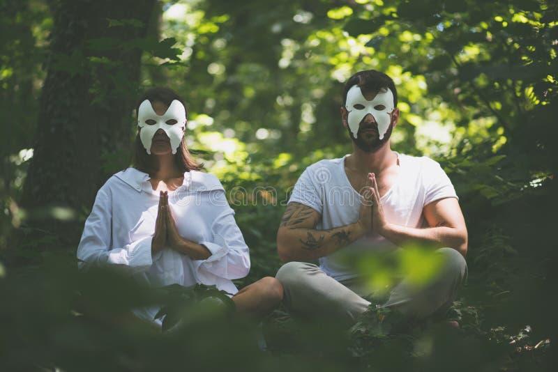Hidden face yoga in nature. Young couple royalty free stock photos