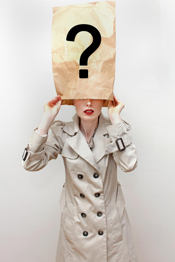 Hidden identity. Young woman in trench coat hides her identity with face covered under paper bag with question mark royalty free stock photography