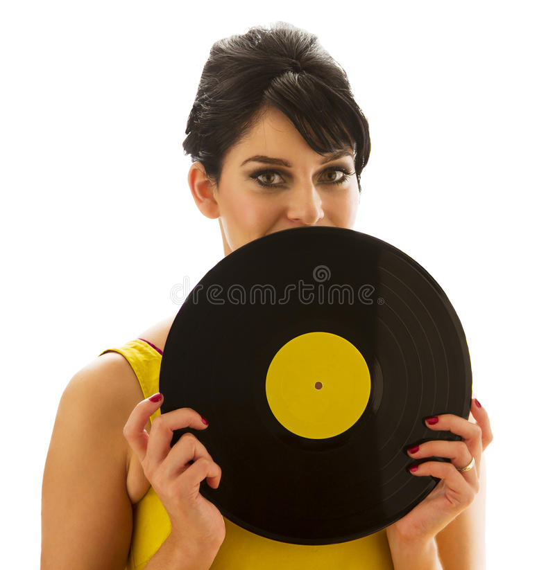Hidding behind a record. Young woman in a yellow dress, looking over a record with a yellow label stock image