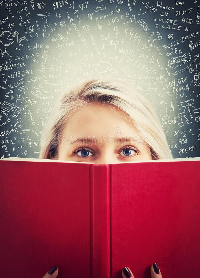 Hide behind a book. Close up portrait of thoughtful looking student girl hiding behind a book. Finding the right answer to difficult mathematics calculation stock images