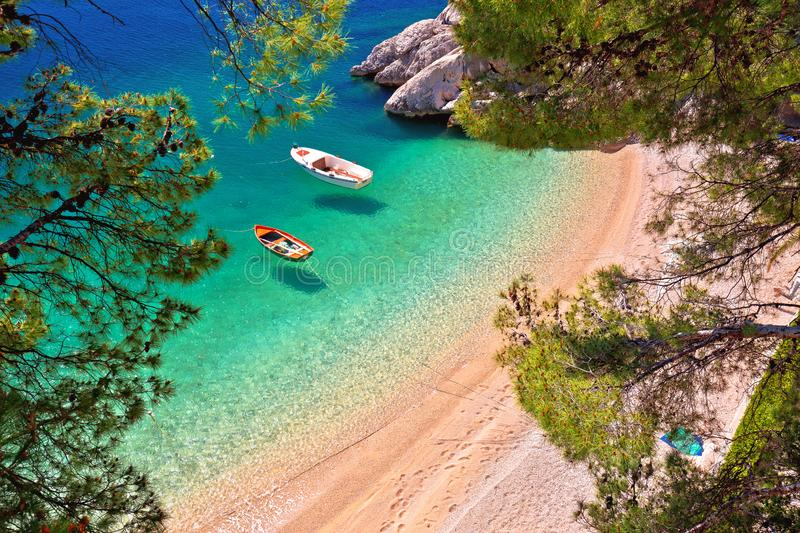 Hiden beach in Brela with boats on emerald sea aerial view stock image
