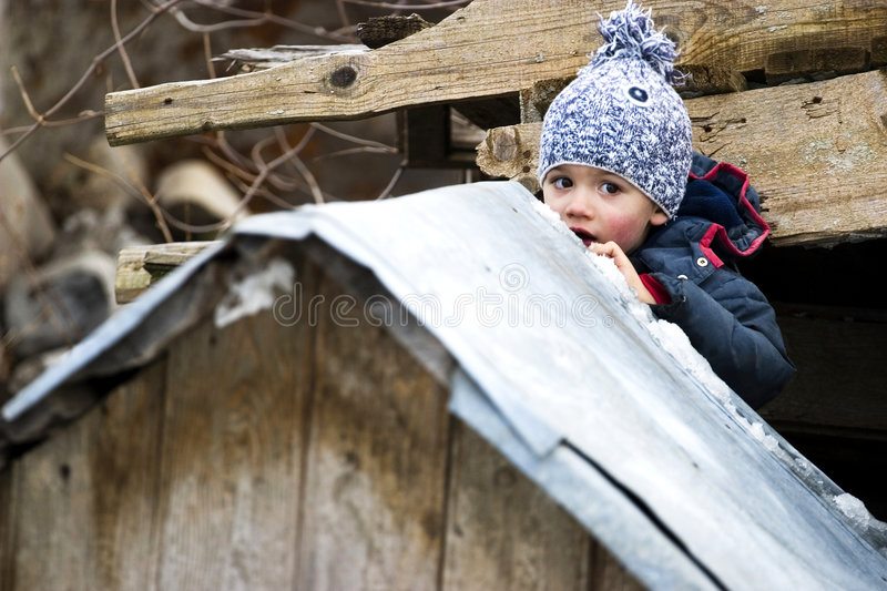 Hiding Child. A playful child hiding behind a wooden structure royalty free stock images