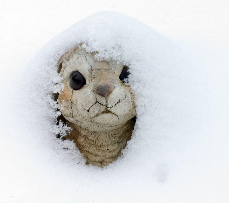 In Hiding. Concrete bunny, a garden decoration, buried in a new winter snow stock photos