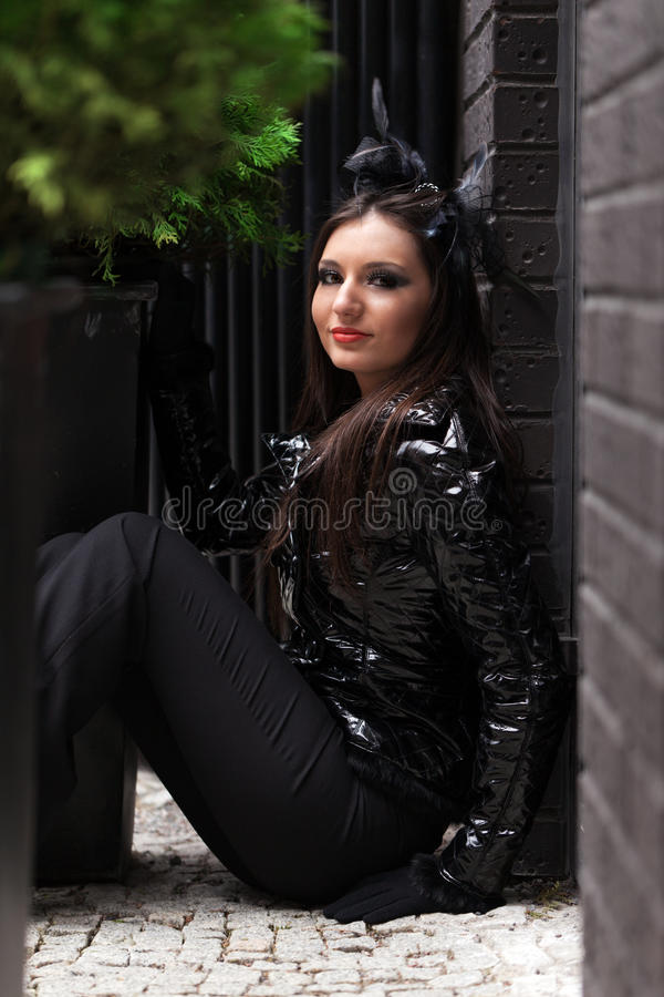 Hiding in the corner. Young fashion-looking girl hiding behind the corner royalty free stock photography