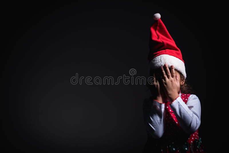 Hiding little Santa. Little Santa hiding his head and waiting for presents,blank space and low key technique royalty free stock photos