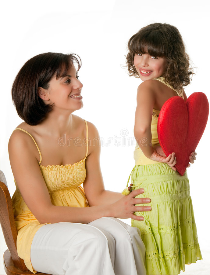 Hiding love. Little girl hiding a big red heart for mother's day royalty free stock photo