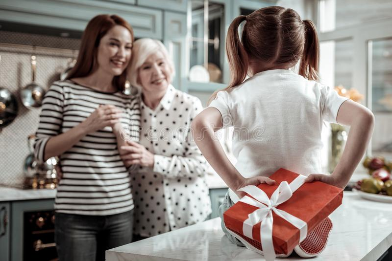 Cute girl sitting on the table and hiding present from mother and granny stock photography