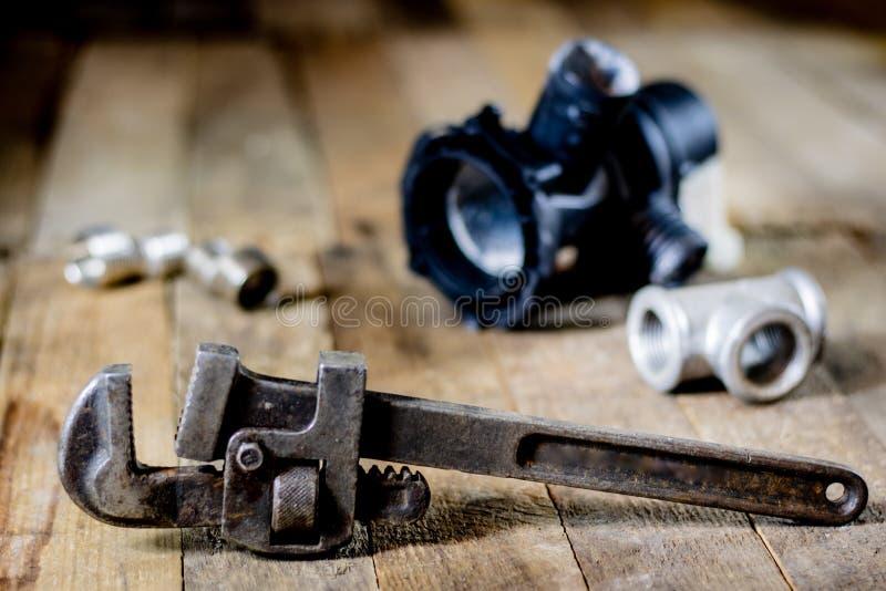 Hidráulica, ferramentas para o encanador na tabela de madeira A oficina, apresenta a imagem de stock