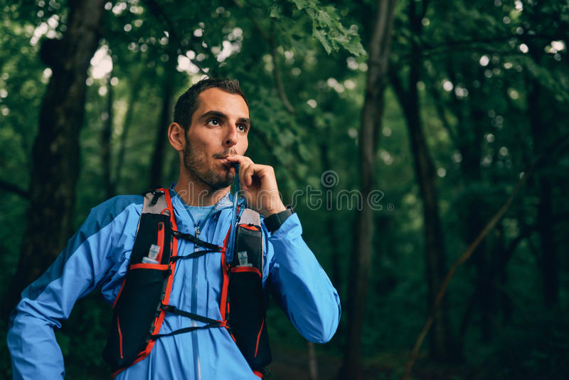 Hidratos masculinos aptos del basculador mientras que entrenamiento del día para la raza del rastro del bosque del campo a través fotografía de archivo