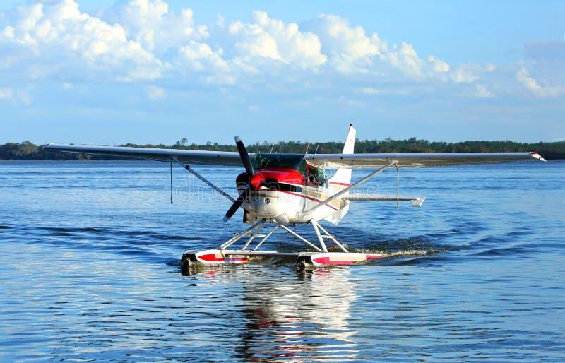 Hidroavião do único motor em águas azuis e em céus azuis no fundo fotos de stock royalty free