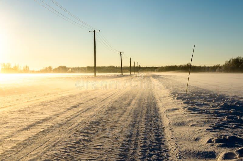 Hiele el camino en un campo congelado en una mañana hivernal nebulosa imagenes de archivo