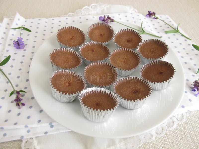 Hiele el chocolate con el polvo de cacao, el azúcar en polvo y el aceite de coco en las mini tazas de aluminio fotos de archivo