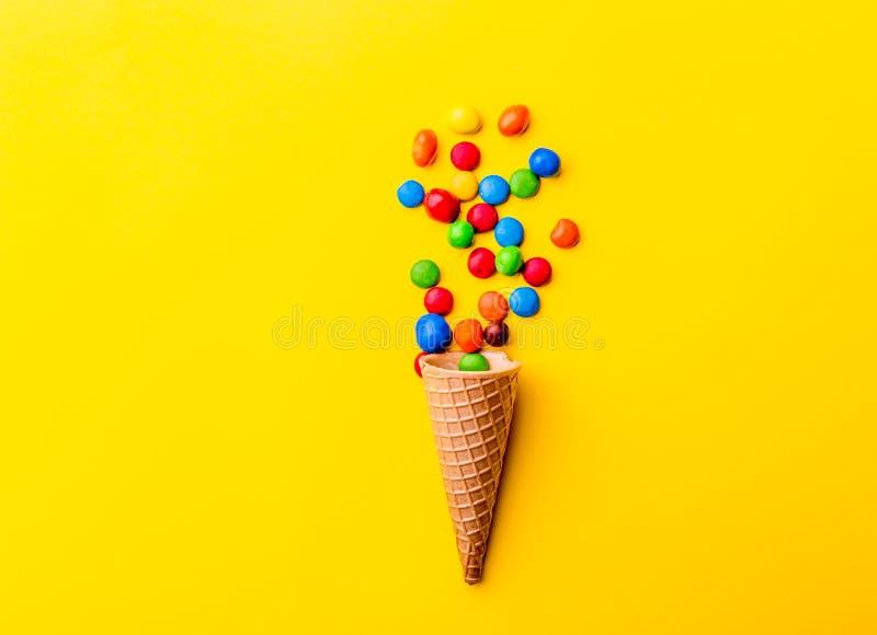 Hiele el cono del creame con el caramelo en fondo amarillo Concepto de Minimalistic imágenes de archivo libres de regalías