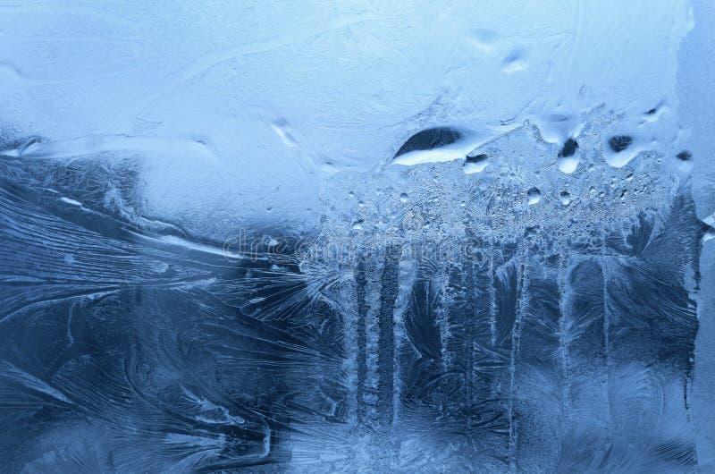 Hiele el modelo y los descensos congelados del agua en el vidrio de la ventana del invierno foto de archivo